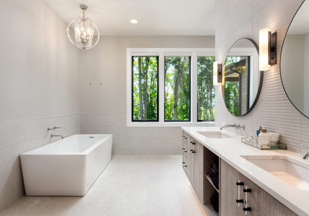 Elegant Bathroom in New Luxury Home with Two Sinks, Bathtub, and Cabinets