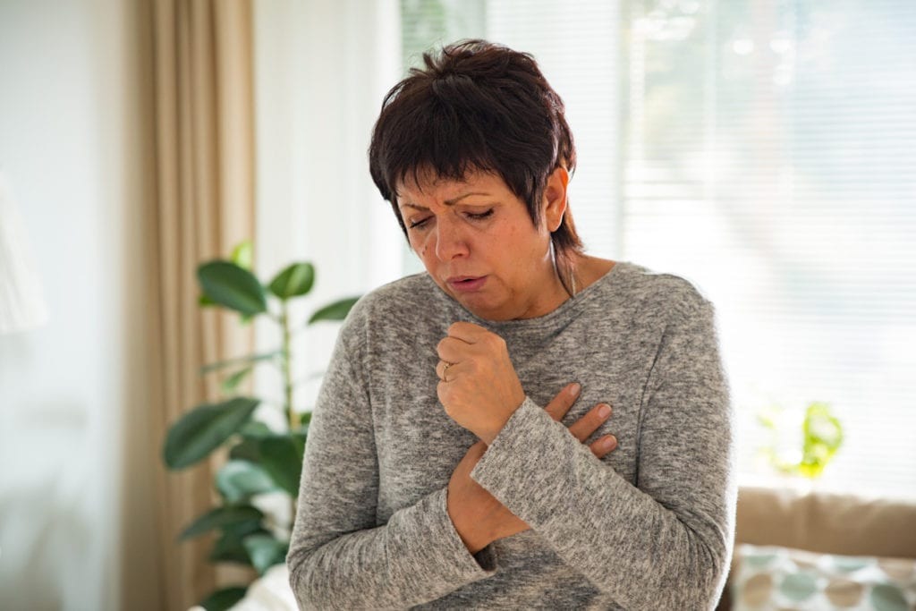 Sick mature woman with sore throat