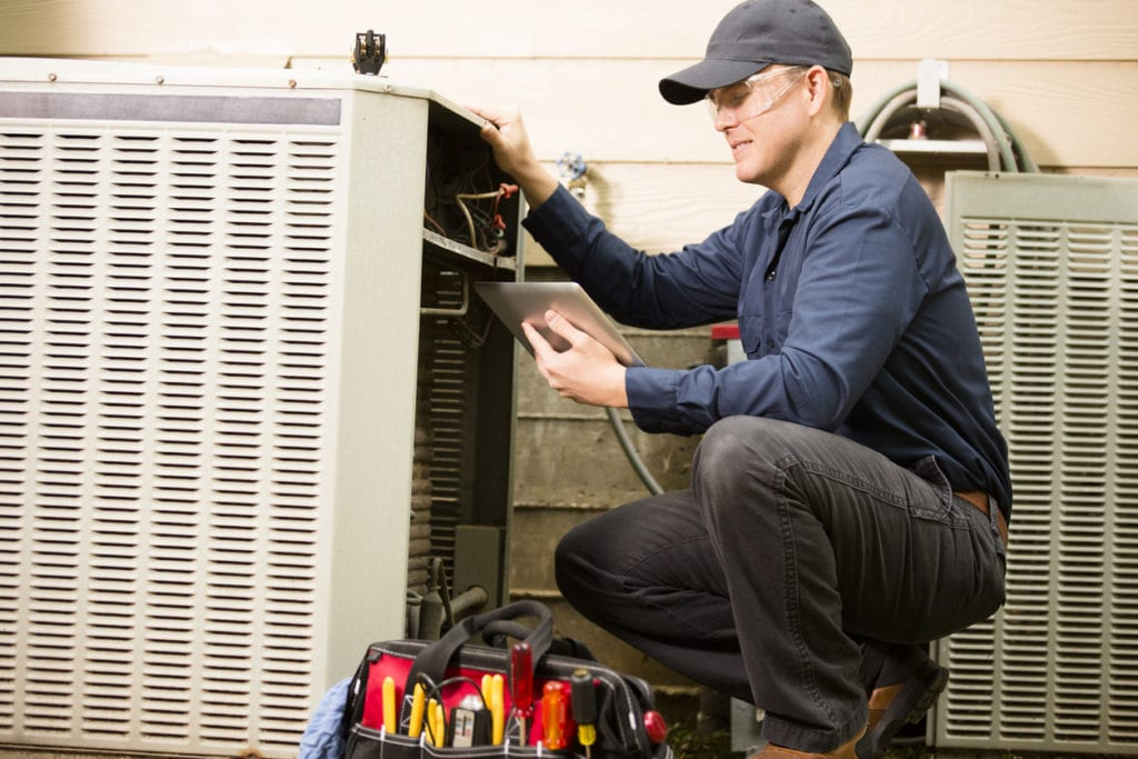 Air conditioner repairman works on home unit. Blue collar worker.