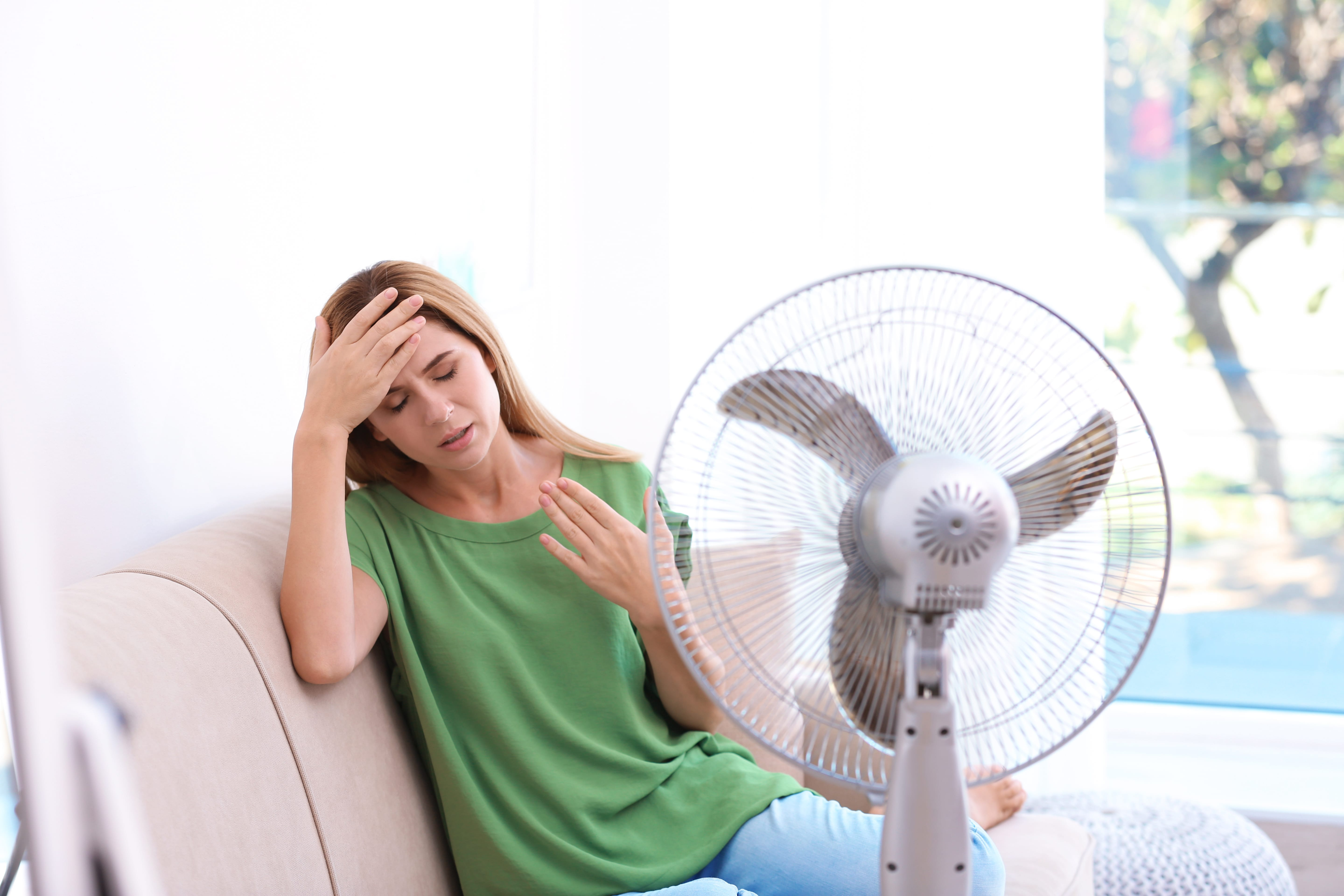 Woman,Suffering,From,Heat,In,Front,Of,Fan,At,Home