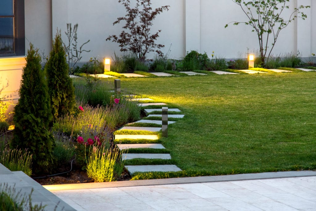 Backyard,Of,The,Mansion,With,A,Flowerbed,And,A,Lawn